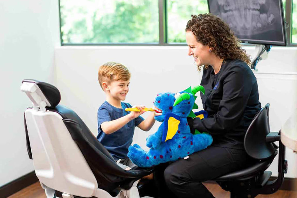 A dental assistant demonstrates good brushing techniques using a stuffed dragon toy to a young dental patient