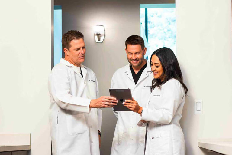 The dentists at Collins Dental have a discussion while standing around an iPad