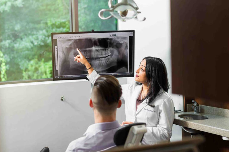 Dr. Azer pointing to x-rays and speaking with a male dental patient who is seated in an exam chair