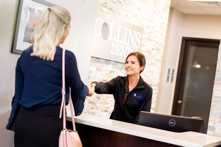 A receptionist at Collins Dental welcomes a patient at the front desk