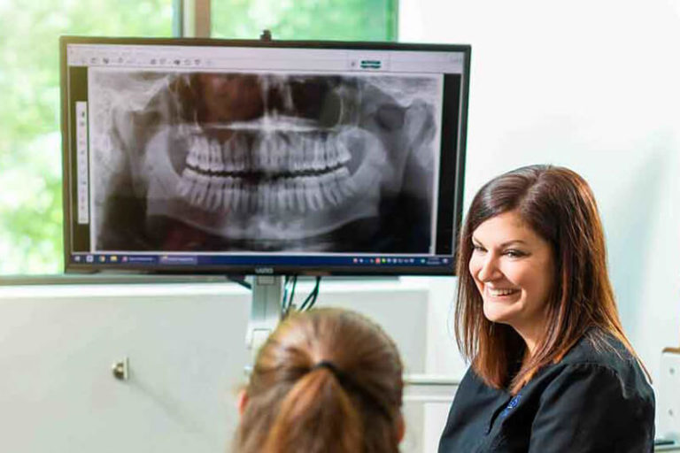 A dental assistant speaks to a patient with digital x-rays on a screen behind her